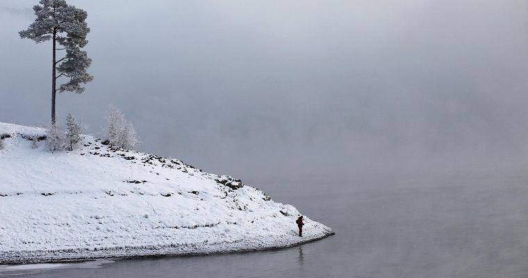 A fisherman stands on the frozen bank of the Yenisei River near Russia's Siberian