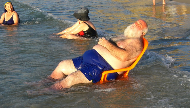 Fat Old Man Balancing On A Chair In The Sea