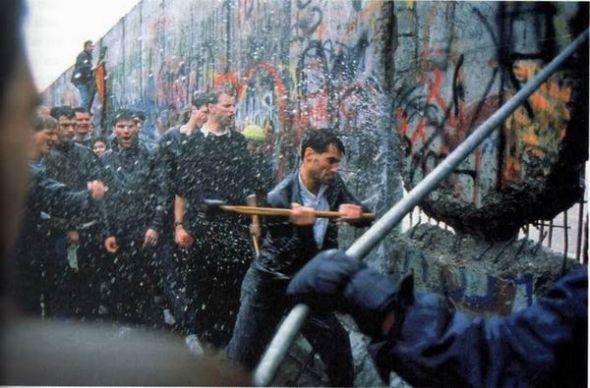 man destroying berlin wall