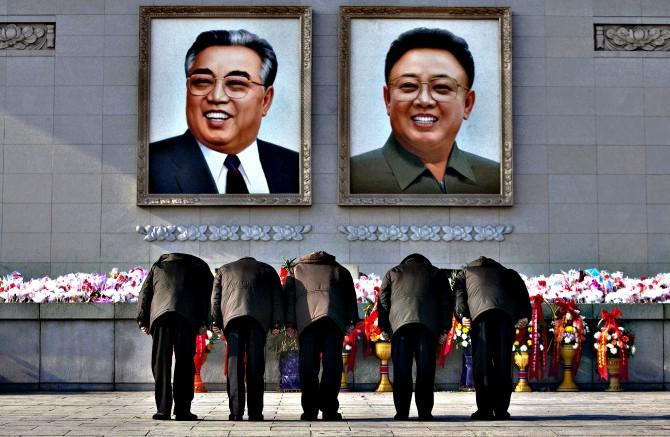 North Koreans bow beneath portraits of the late leaders Kim Jong