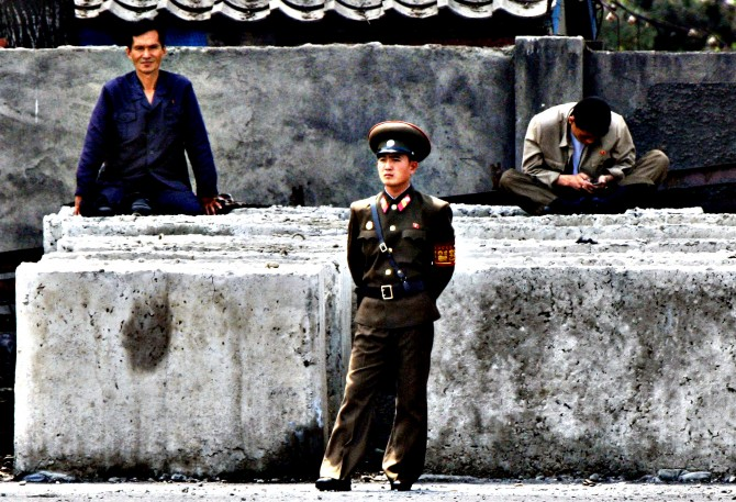 A North Korean worker checks his mobile phone as a soldier stand