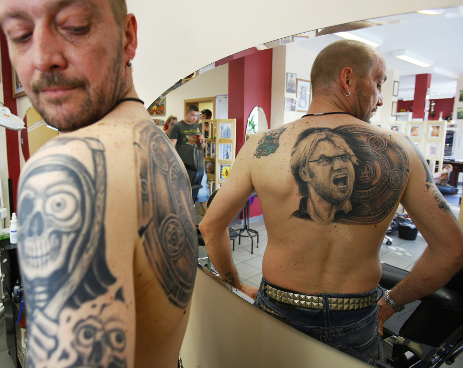 Soccer fan admires his new tattoo of Germany's soccer trophy and Borussia Dortmund coach Klopp at tattoo shop in Unna