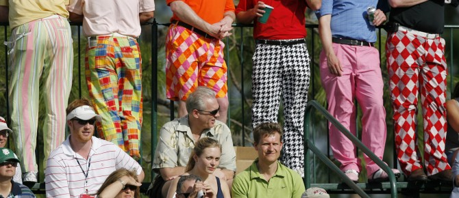 Male spectators wearing colorful retro golf trousers watch from the stands on the 17th hole during third round play at the Arnold Palmer Invitational golf tournament at the Bay Hill Club in Orlando