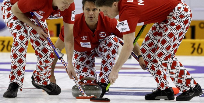 Norway skip Thomas Ulsrud delivers his stone as Loevold and Nergaard sweep during play against Sweden at the World Men's Curling Championship 2012 in Basel