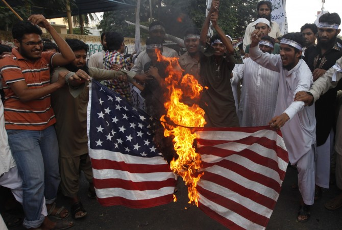 Supporters of the Jamaat-ud-Dawa Islamic organization burn the U.S. flag as they shout slogans during a protest, against U.S. drone attacks in the Pakistani tribal region, in Karachi