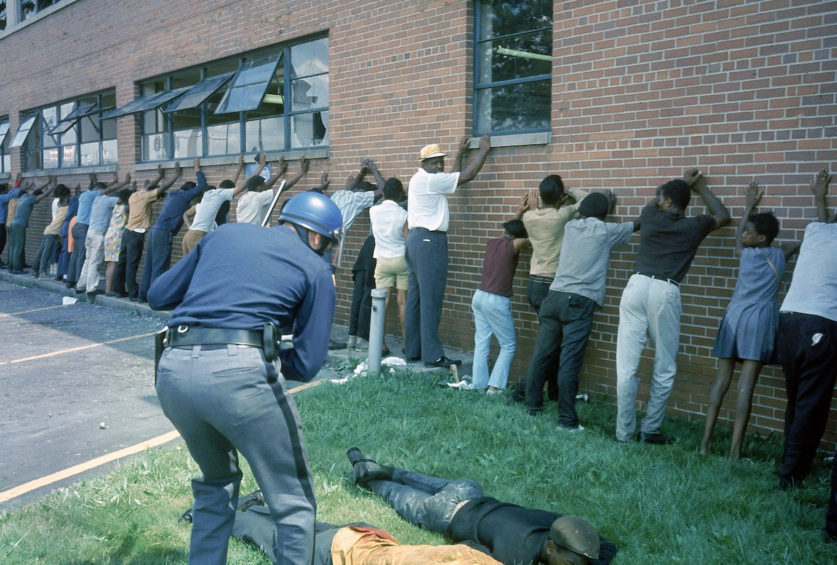 Policeman lining up suspects after race riots.
