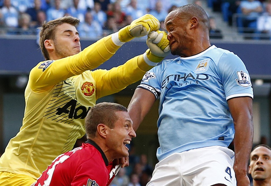 Manchester City's Kompany gets hit in his face as he is challenged by Manchester United's David de Gea during their English Premier League soccer match in Manchester