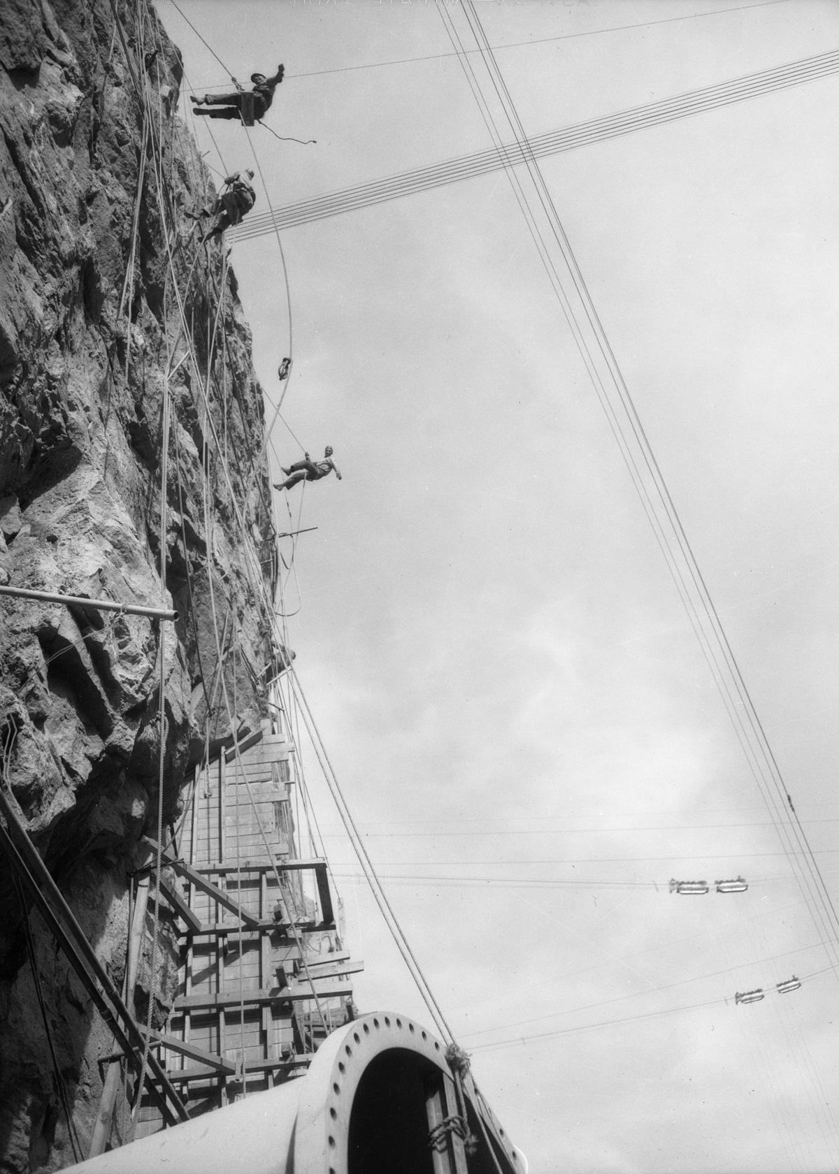 1934 --- Contruction workers rappel down cliff face dw-1934-12-08-70~09 --- Image by © Dick Whittington Studio/Corbis