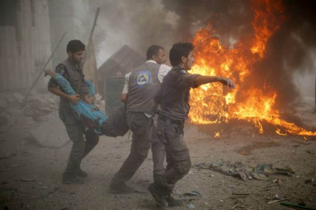 Syrian emergency personnel carry a wounded man following air strikes by Syrian government forces on a marketplace in the rebel-held area of Douma, east of the capital Damascus, on August 16, 2015. At least 70 people were killed and 200 people were injured, with the death toll -most of them civilians- likely to rise as many of the wounded were in serious condition, the Syrian Observatory for Human Rights said. AFP PHOTO / SAMEER AL-DOUMYSAMEER AL-DOUMY/AFP/Getty Images