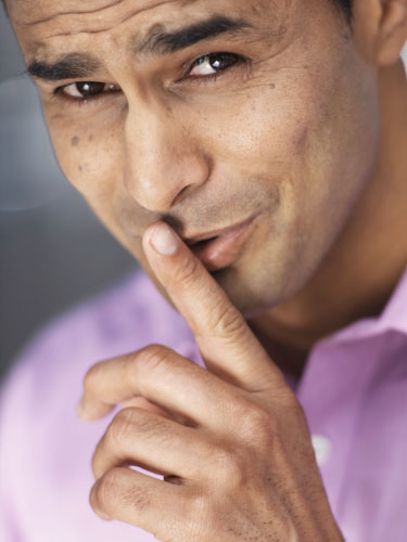 Close-up portrait of a man putting his finger to his lips