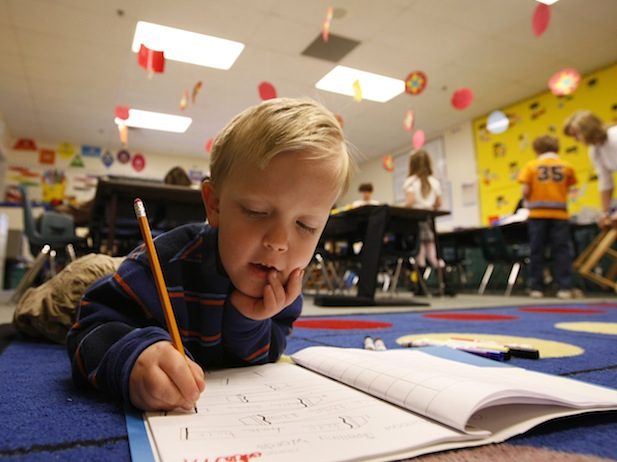 First grader Adam Kotzian does his writing work on the floor of his classroom at Eagleview Elementary school in Thornton, Colorado March 31, 2010.  Adam and his parents are achondroplasia dwarfs but his sister Avery is not.  To match feature LIFE DWARFISM   REUTERS/Rick Wilking (UNITED STATES)