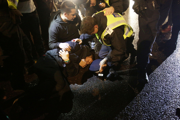 A photographer lays on the floor, after being hit by an Aston Martin which was surrounded by protestors in Lower Grosvenor Place, near Victoria in London, during the Million Mask March bonfire night protest organised by activist group Anonymous.