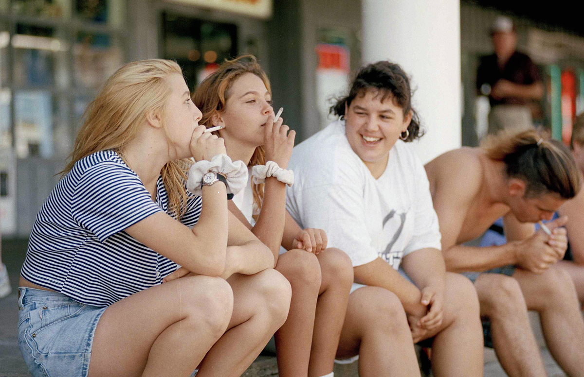 """Kristi Deyo, 16, left, Wendy Miller, 15, center, and Monica Rieck, 16, right, all of Hampton Beach, New Hampshire, hang out with friends and smoke cigarettes, Aug. 10, 1995. In a dramatic assault on cigarette use, President Clinton today declared nicotine a drug and ordered a crack-down on childhood smoking to """"free our teenagers from addiction and dependency."""" (AP Photo/Susan Walsh)"""