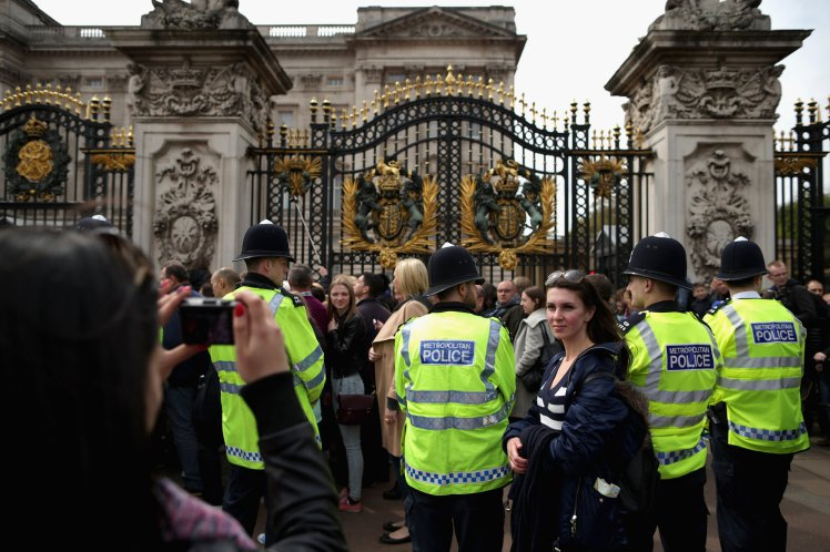 LONDON, UNITED KINGDOM - MAY 02: Tourists pose for photographs as Metropolitan Police officers keep an eye on the thousands of people lined up for a chance to glimpse and photograph the announcement of the birth of Prince William, Duke of Cambridge and the Duchess of Cambridge's second child outside Buckingham Palace on May 2, 2015 in London, United Kingdom. Catherine, Duchess of Cambridge delivered the baby girl at 8:34am Saturday and she is the fourth in line to the throne and the Queen's fifth great-grandchild. (Photo by Chip Somodevilla/Getty Images)