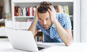 Worried man looking on laptop