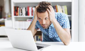 Worried man looking on laptop