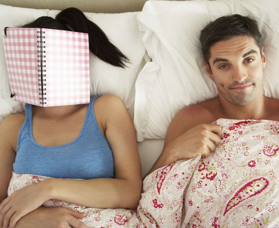 Bored Looking Man Lying In Bed Next To Woman