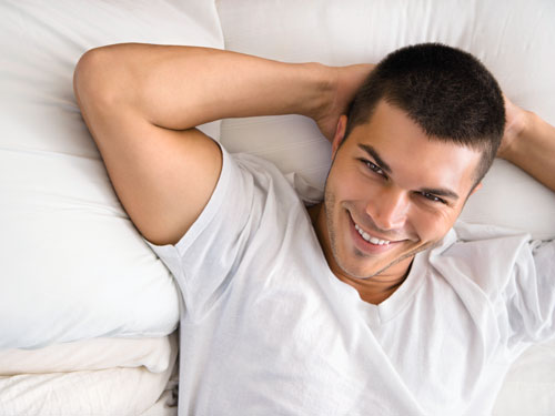 High angle view of handsome Caucasian mid adult man lying with hands behind head smiling.