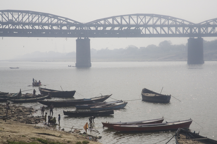 Ganges river shore wooden boats and iron bridge