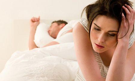 man woman bed worried