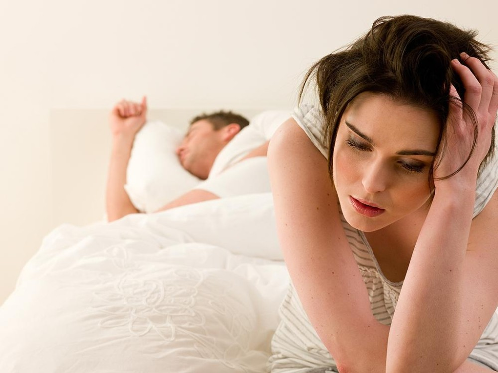 man woman bed worried