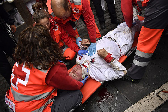 A injured reveler is tended to by medics on the Estafeta corner during seventh running of the bulls with Nunez del Cubillo's ranch bulls at the San Fermin Festival, in Pamplona, northern Spain, Wednesday, July 13, 2016. Revelers from around the world flock to Pamplona every year to take part in the eight days of the running of the bulls. (AP Photo/Alvaro Barrientos)