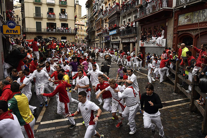 Revelers run around Nunez del Cubillo's fighting bulls on the Estafeta corner during the seventh running of the bulls at the San Fermin Festival, in Pamplona, northern Spain, Wednesday, July 13, 2016. Revelers from around the world flock to Pamplona every year to take part in the eight days of the running of the bulls. (AP Photo/Alvaro Barrientos)