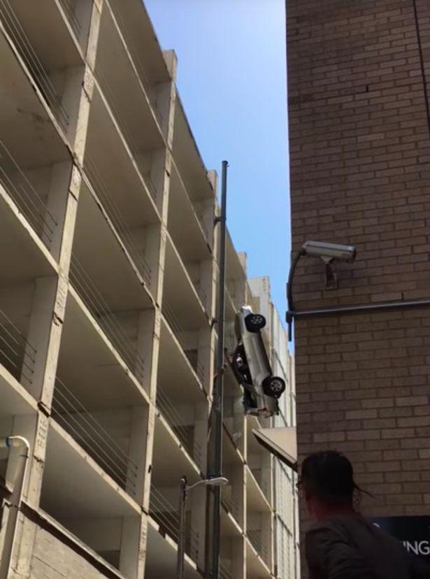 driver-crawls-out-of-car-dangling-off-side-of-parking-garage