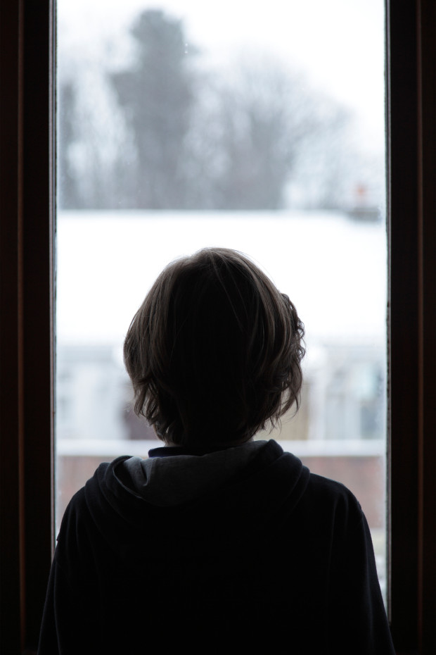 A boy looking at snow through a window, UK