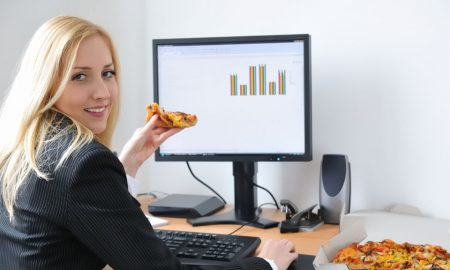 Woman eating pizza at work