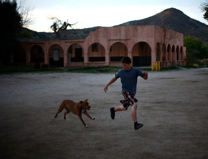 A dog chases a boy in Jacumba, California November 7, 2010. Jacumba is a small border town of less than 1,000 people known mainly for its hot springs. The town, located about a half a mile from the border in unincorporated San Diego county, does not have a port of entry into Mexico, though residents say there is significant illegal immigrant and drug traffic through the town.