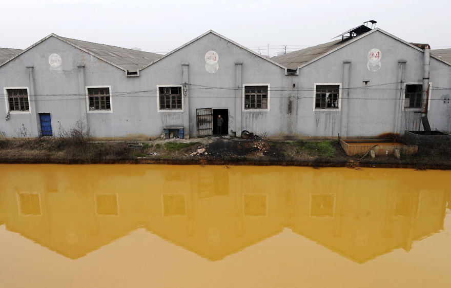 A worker looks at a photographer from a door of a factory manufacturing screws and nuts next to a polluted river in Jiaxing, Zhejiang province March 15, 2012. China's continuing reliance on heavy industry meant it failed to meet its own targets for cleaning its air and water in 2011, the head of the top planning agency told journalists on Monday. REUTERS/Stringer (CHINA - Tags: ENVIRONMENT BUSINESS) CHINA OUT. NO COMMERCIAL OR EDITORIAL SALES IN CHINA - RTR2ZD8N
