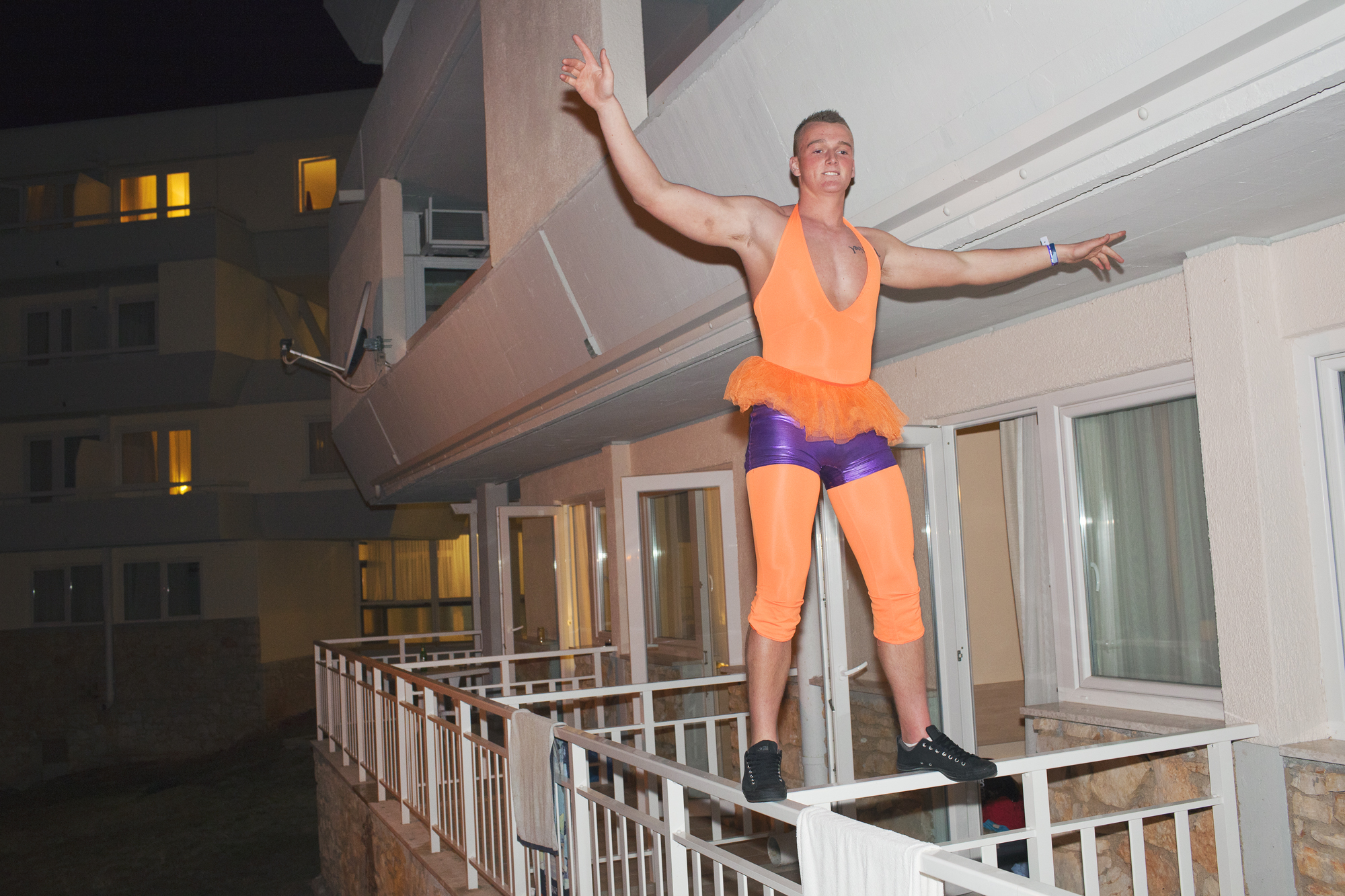 A British University Student balances on a balcony while on the inaugural ILOVETOUR to the town of Porec in Croatia. The tour organizes various sports and themed events and club nights.
