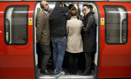 Commuters board an underground train at Kings Cross St Pancras station in London