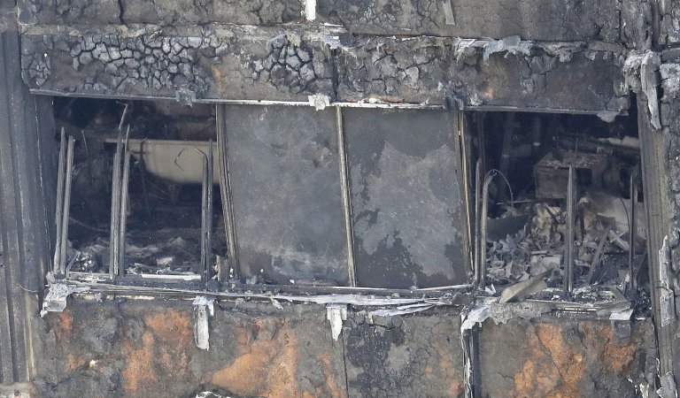 Part of the scorched facade of the Grenfell Tower in London as firefighting continue to damp-down the deadly fire, Thursday, June 15, 2017. A massive fire raced through the 24-storey high-rise apartment building in west London early Wednesday, and London fire commissioner says it will take weeks for the building to be searched and 'cleared'. (AP Photo/Frank Augstein)