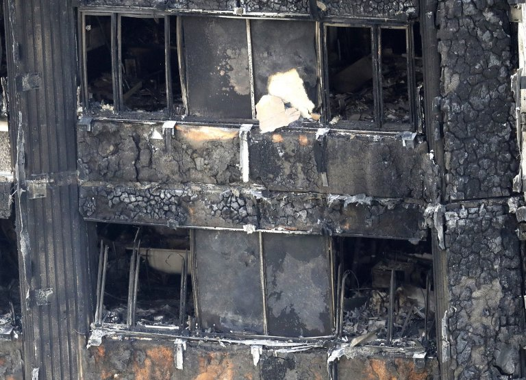 Part of the scorched facade of the Grenfell Tower in London as firefighters continue to damp-down the deadly fire, Thursday, June 15, 2017. A massive fire raced through the 24-storey high-rise apartment building in west London early Wednesday, and London fire commissioner says it will take weeks for the building to be searched and 'cleared'(AP Photo/Frank Augstein)