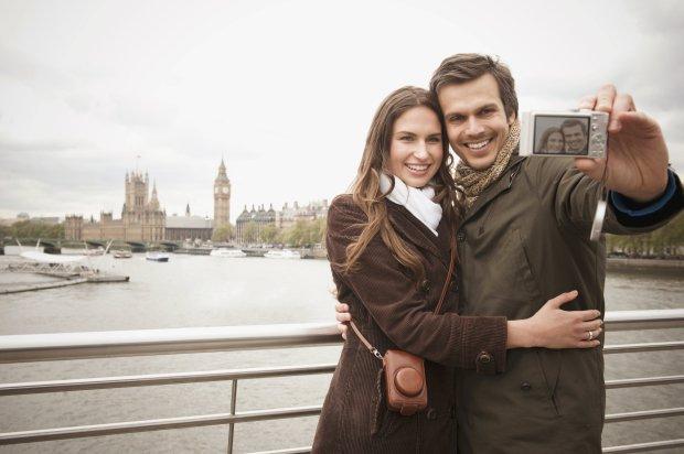 Couple taking selfie on urban bridge near city skyline, London, Middlesex, United Kingdom