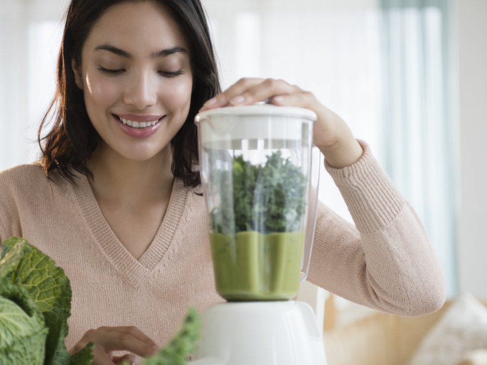 Hispanic woman blending healthy smoothieHispanic woman blending healthy smoothie
