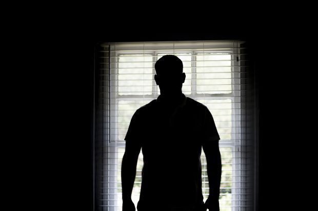 Silhouette of a man by a window