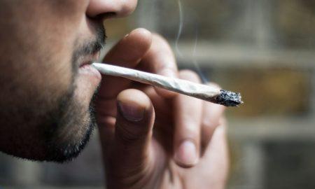 Close-up of an Asian man smoking marijuana joint