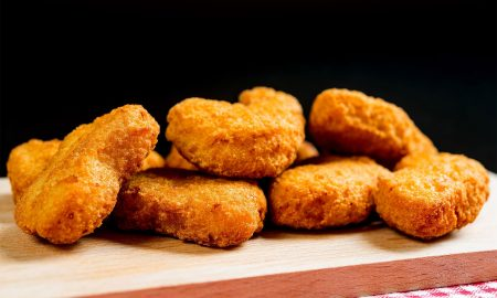 Close-Up Of Chicken Nuggets On Cutting Board Against Black Background